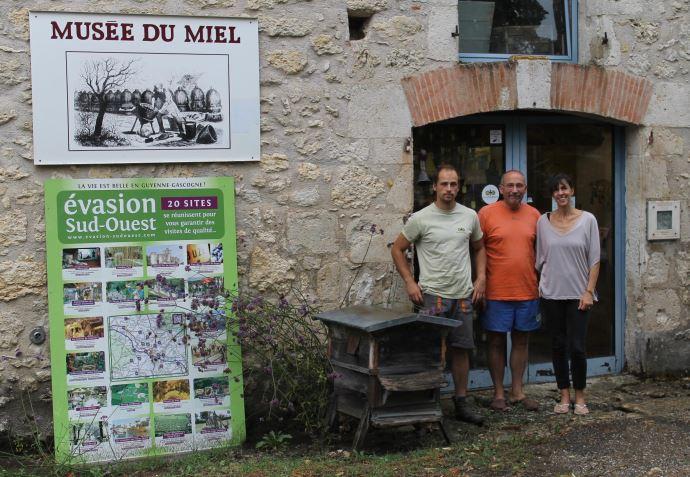 Chantal, Émile et Aymeric devant l'entrée du Musée du miel.