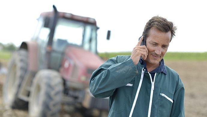 agriculteur avec un telephone portable dans un champ